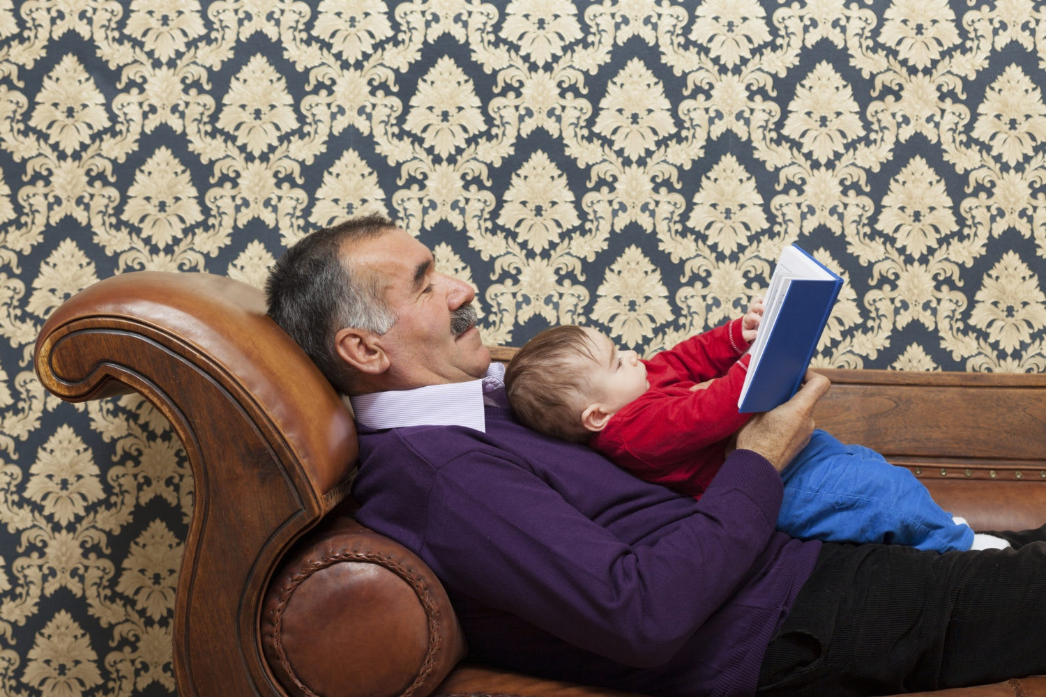 grandfather reading book for newborn grandson on  a sofa