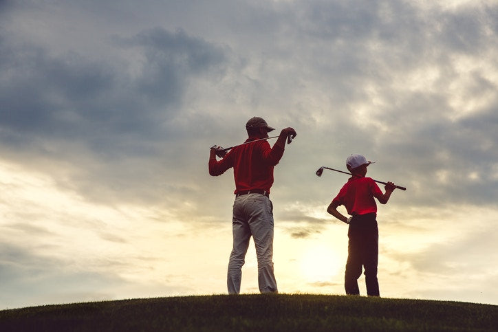 A father and his child playing golf and watching  the sky