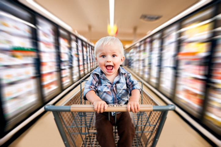 A child sitting on a shopping cart moving fast