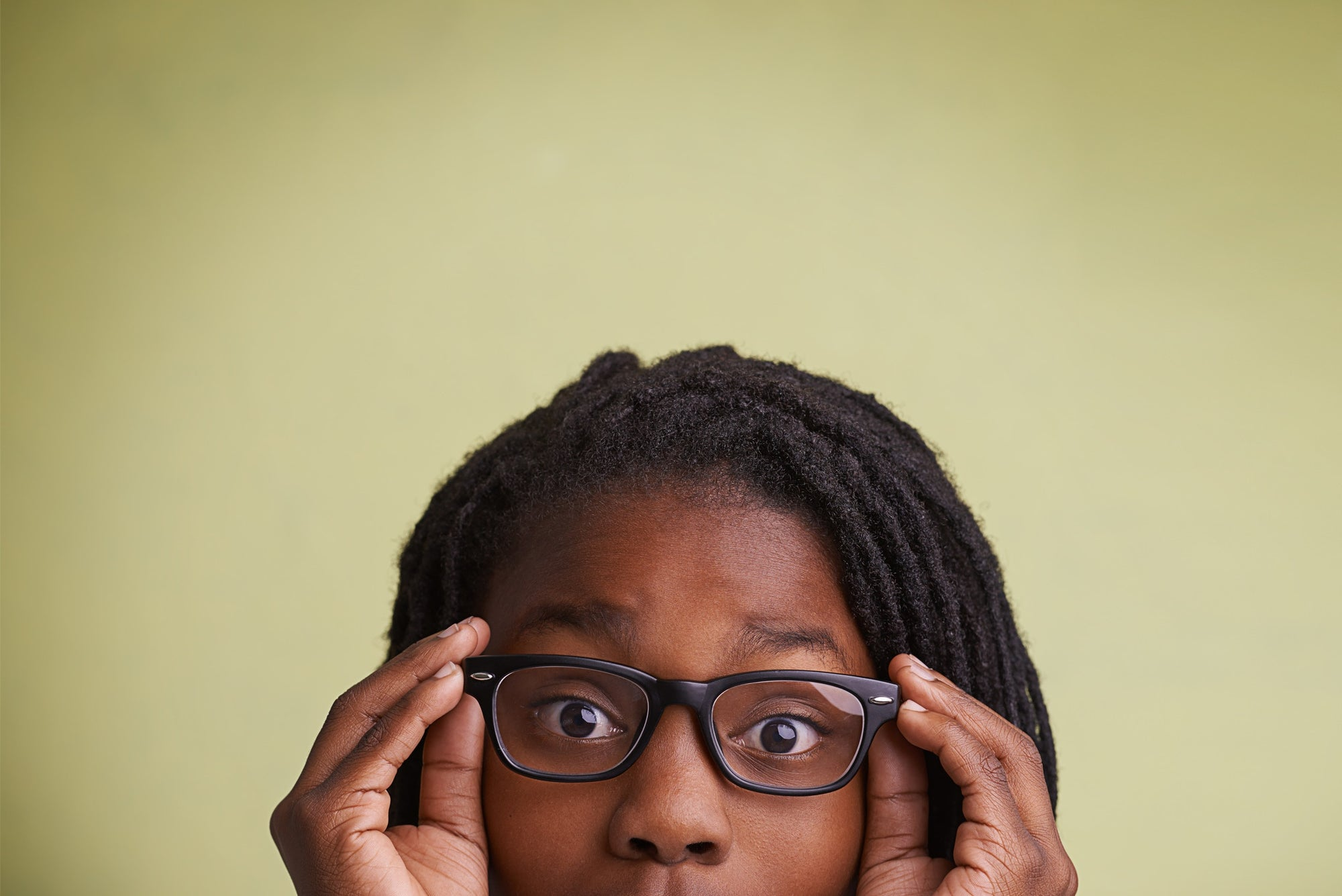 young girl holding her spectacles