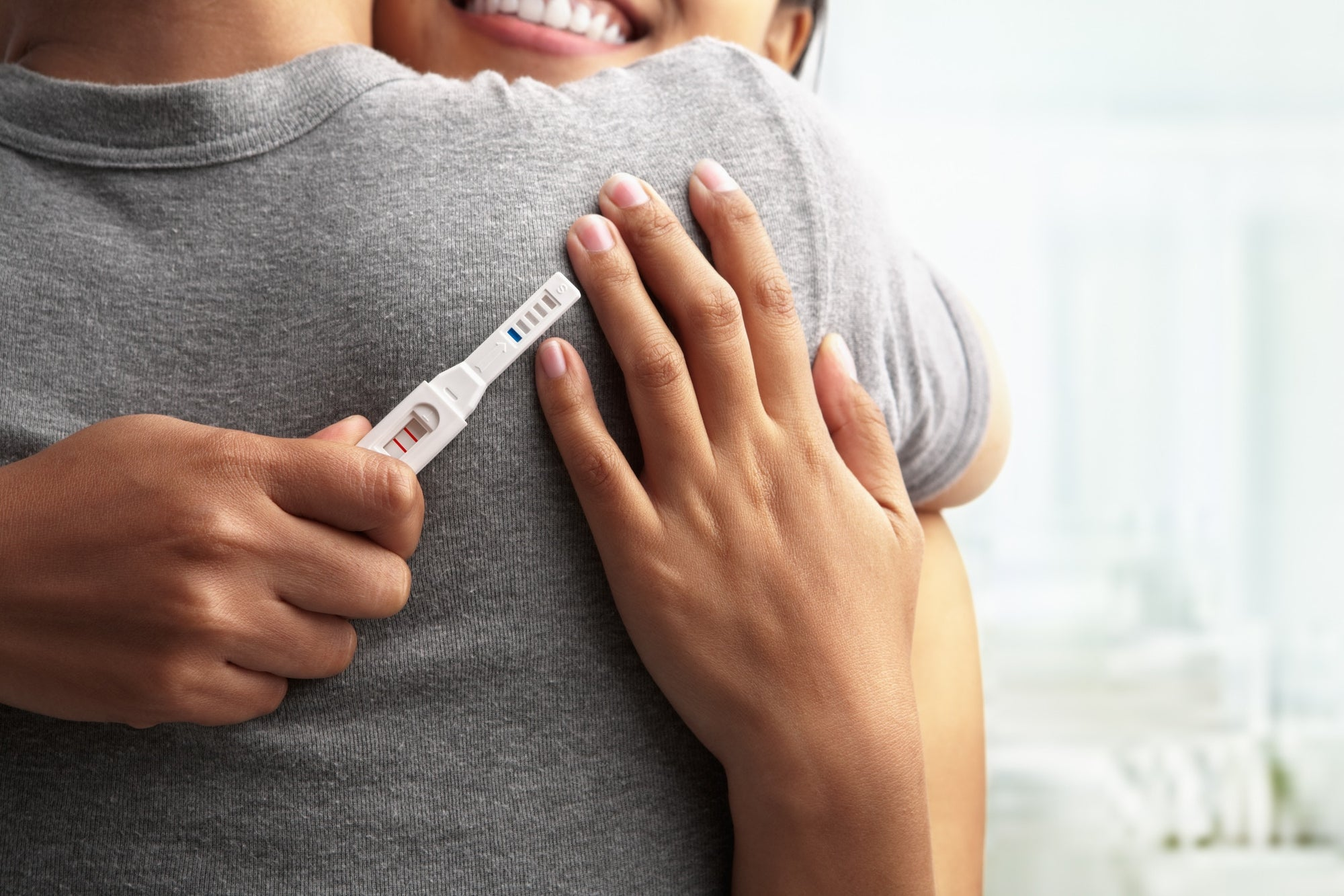 Young happy women hugging husband holding positive result pregnancy test