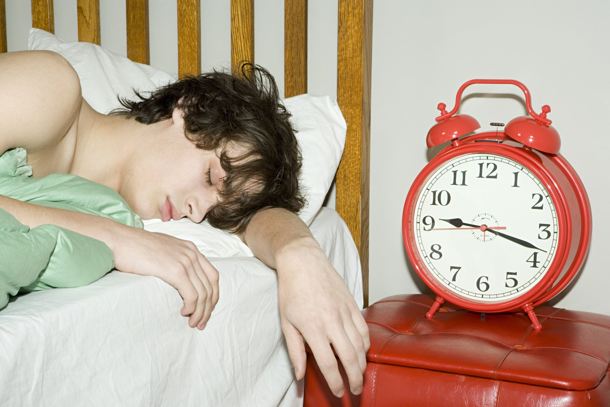 A person sleeping in a bed beside an alarm clock