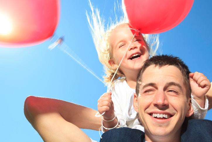 young girl sitting on daddy with two balloons.