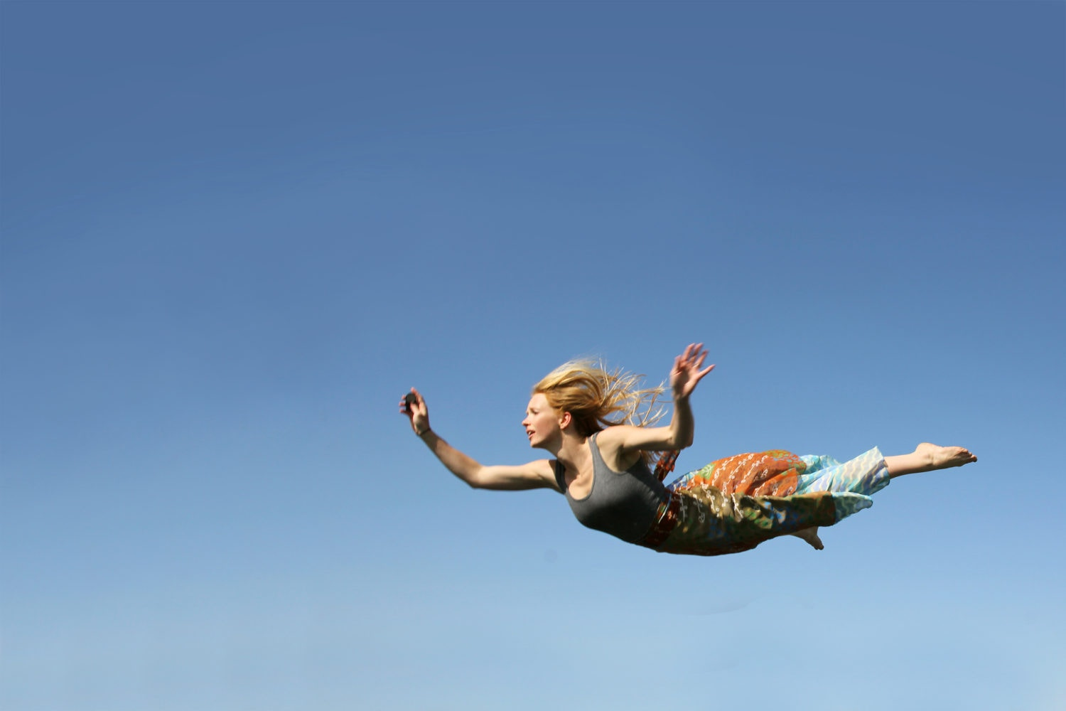 young woman with blonde hair flying or falling through the air