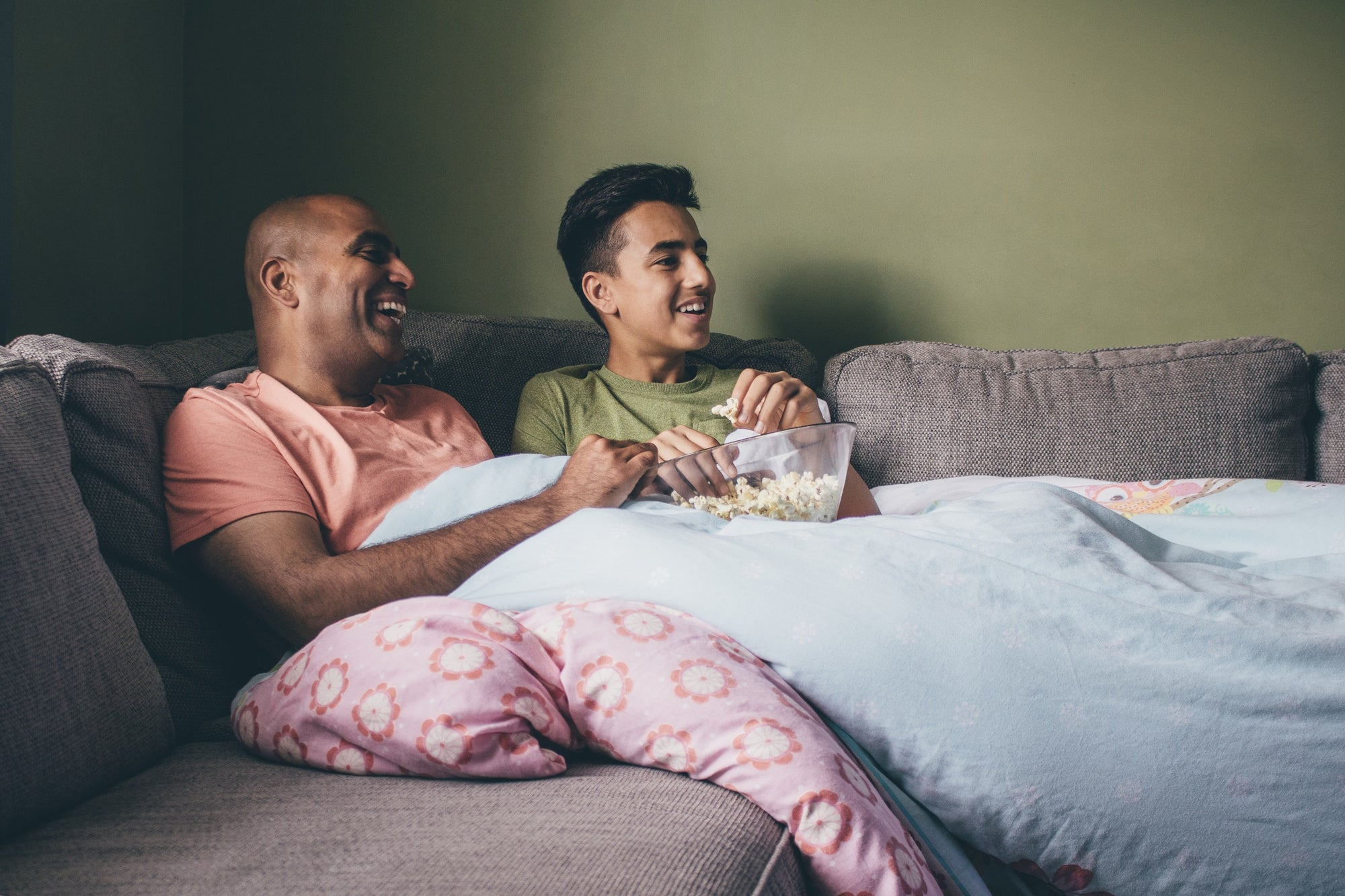 father and son watching tv and eating popcorn on sofa at home