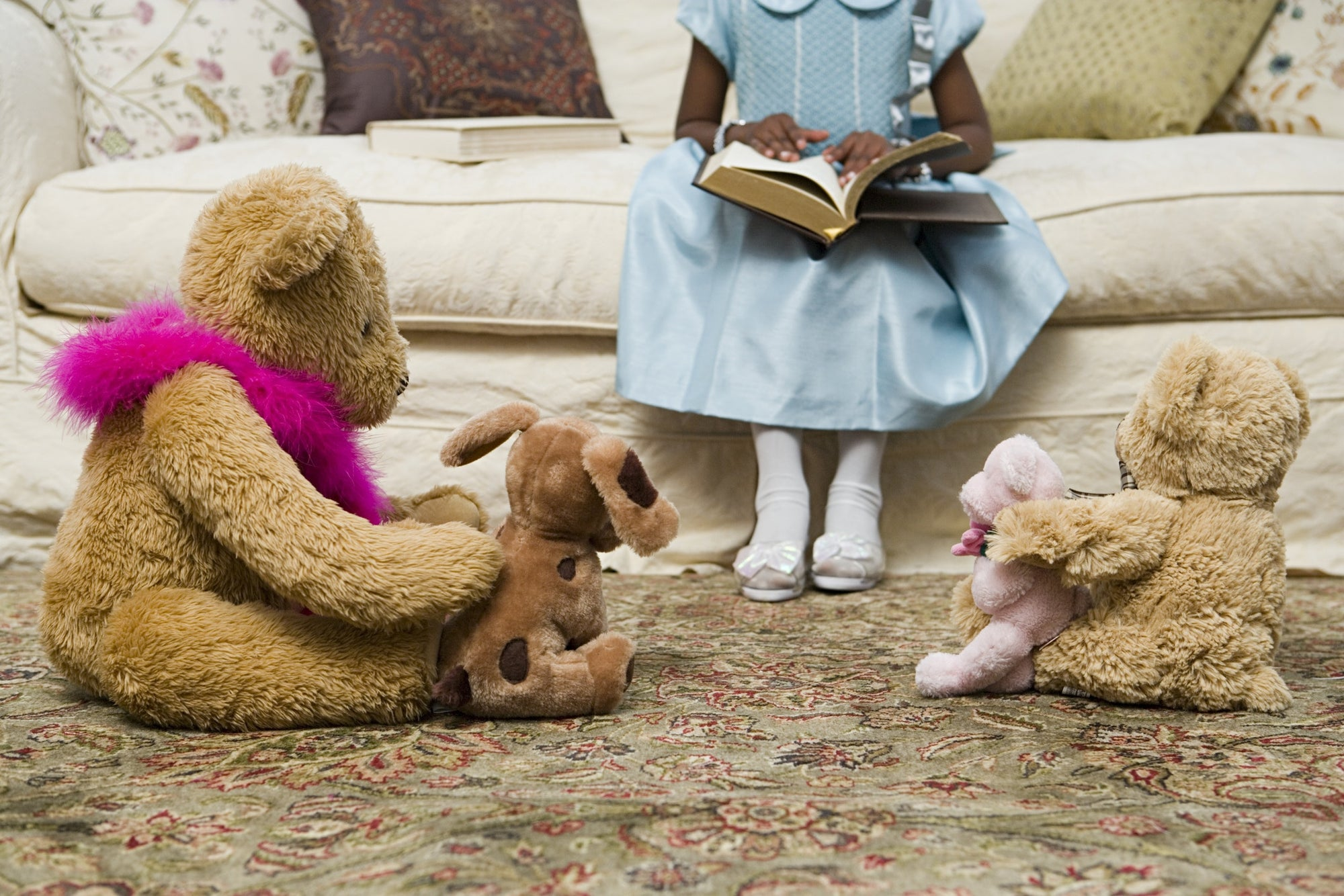 young girl sitting on sofa with book and teddy bear on floor