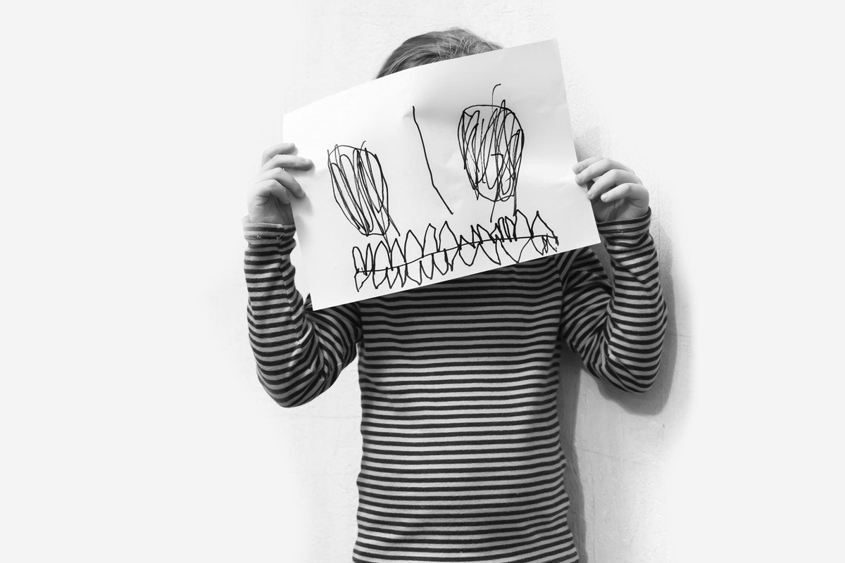 little girl cover her face  with drawing on paper