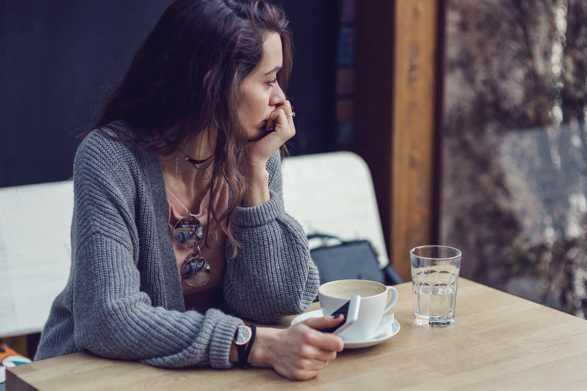 Woman sitting in a restaurant holding her mobile phone looking away