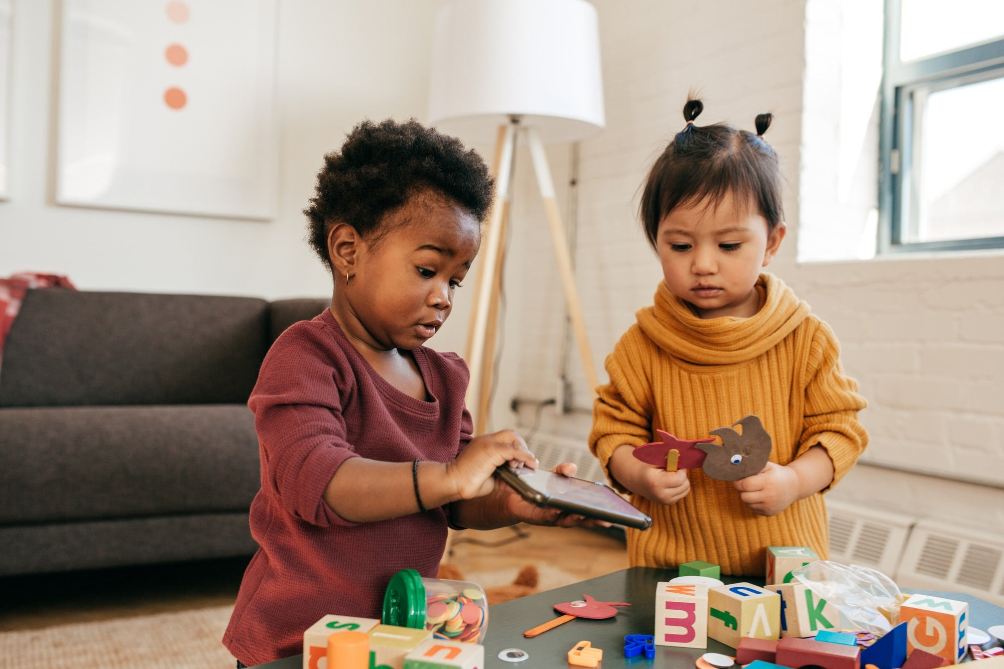 Two young sisters playing with toys on table