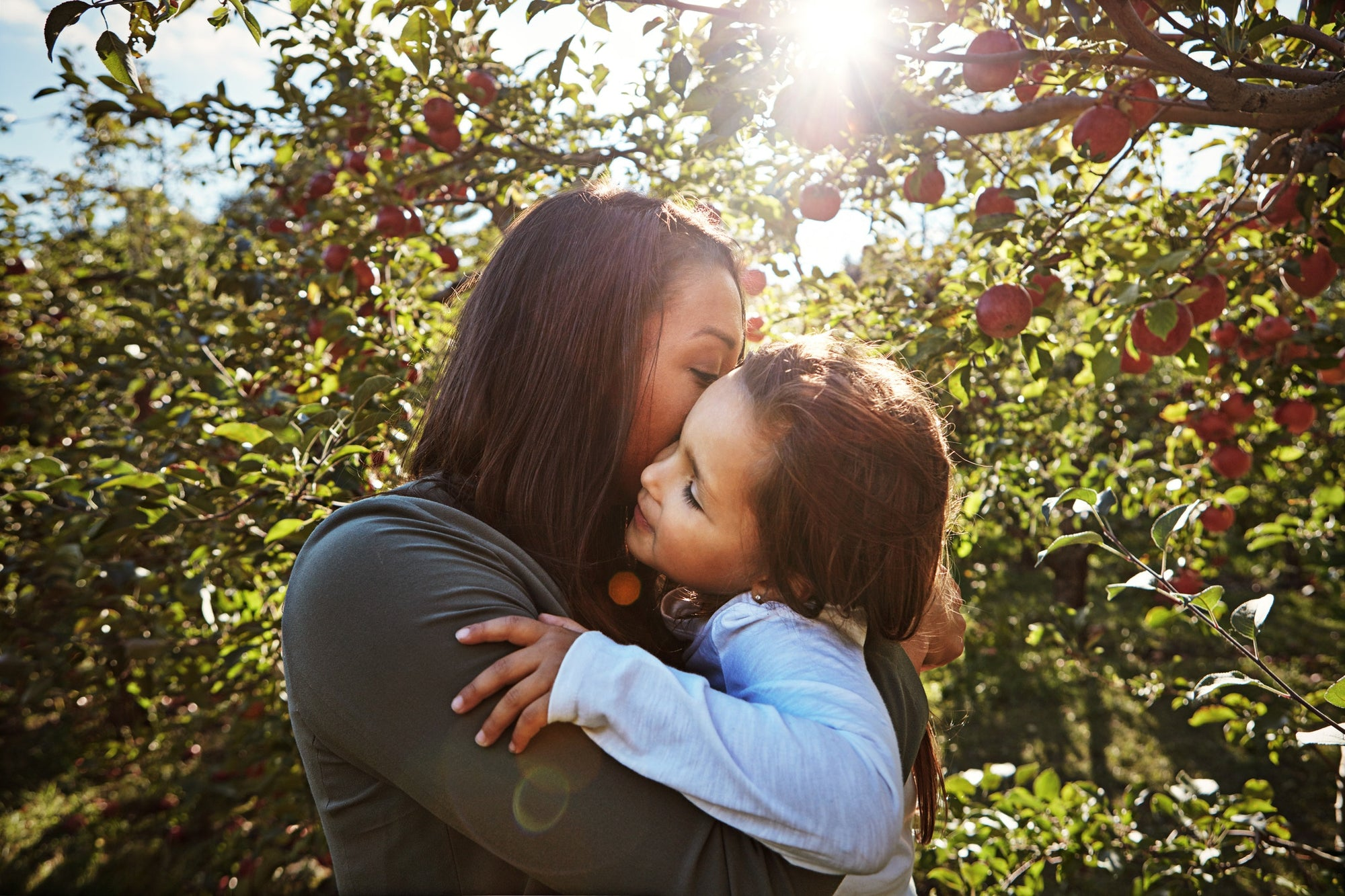 mother is kissing her daughter on the cheek, apple trees on the background