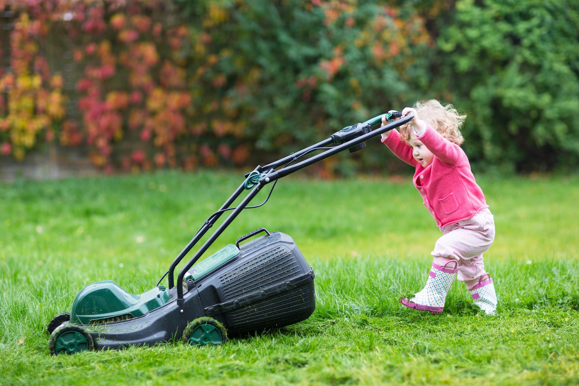 Cute curly baby girl  with big green lawn mower