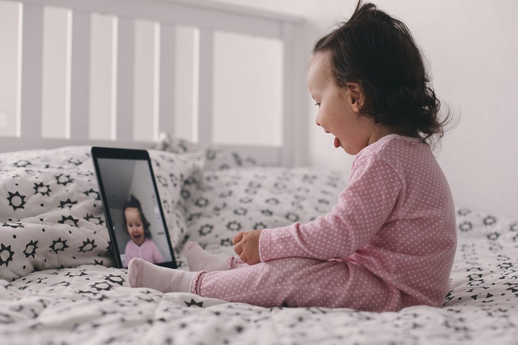 baby sitting on the bed communicates on video call