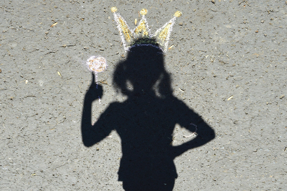 shadow of a girl with a crown and holding lollipop on a road