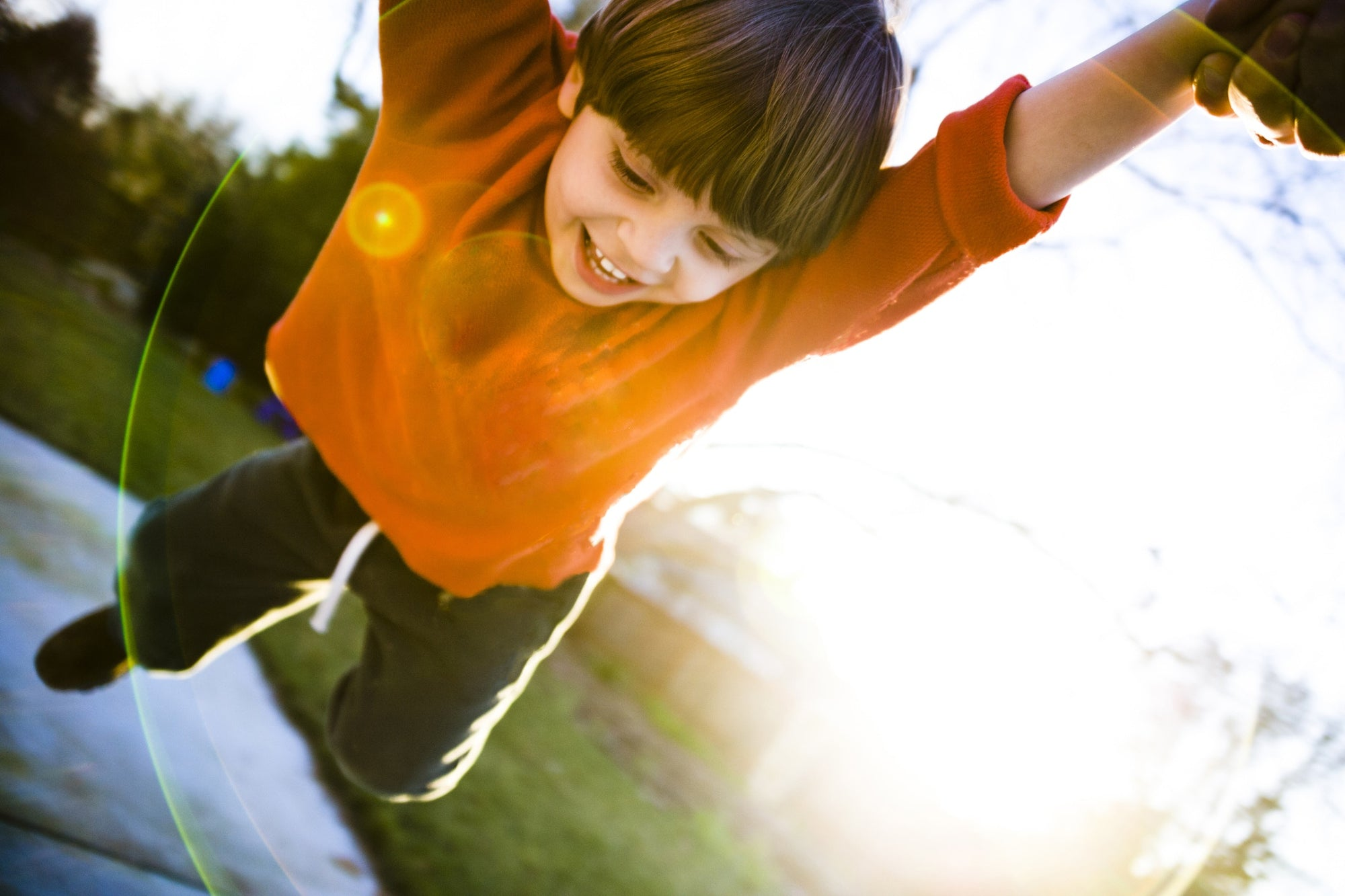 young cheerful boy in orange sweatshirt palying in playground