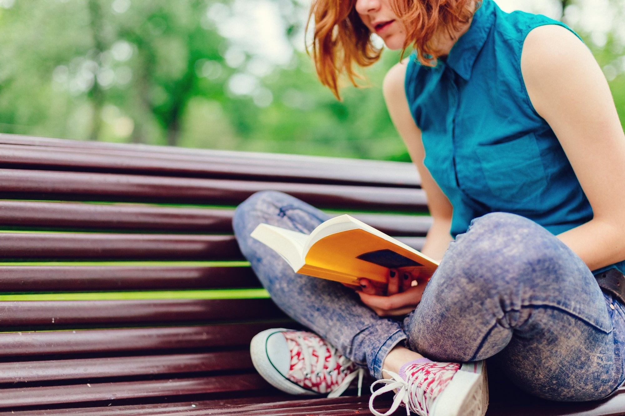 Young woman sitting on a bench in the park and reading book