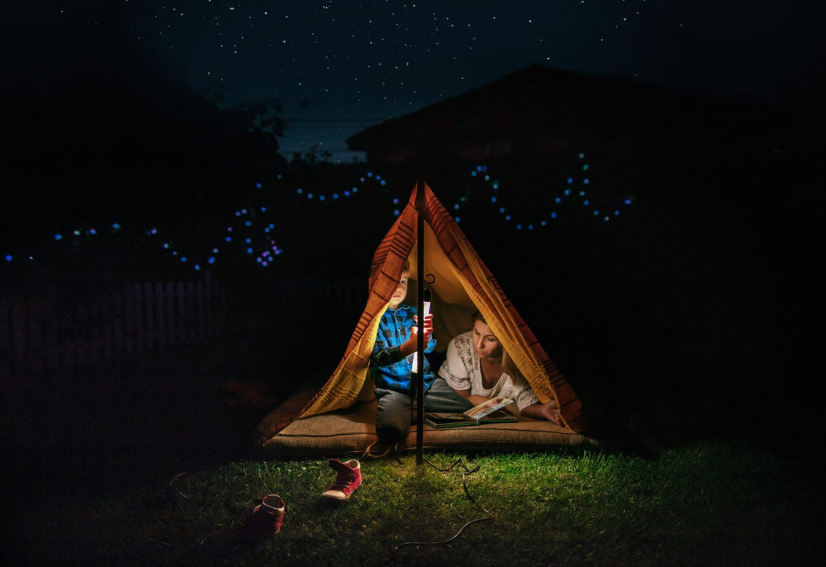 Mother and son reading a bed time story on a tent at home