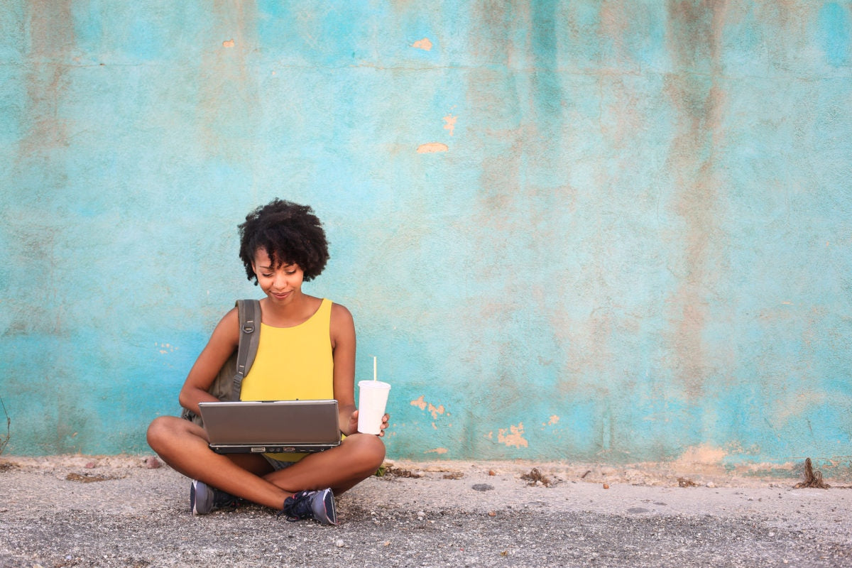 A woman sitting on the road and using laptop