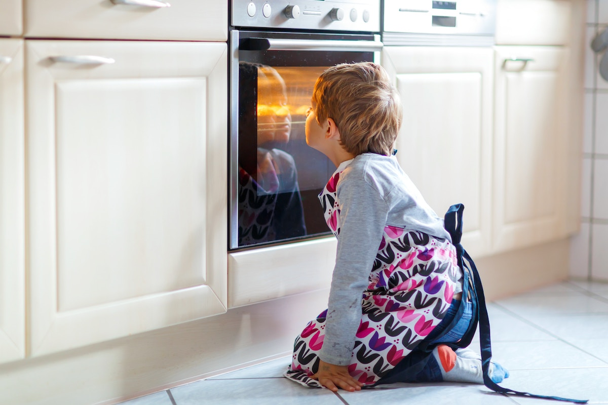 Young boy sitting in front of oven, looking through glass