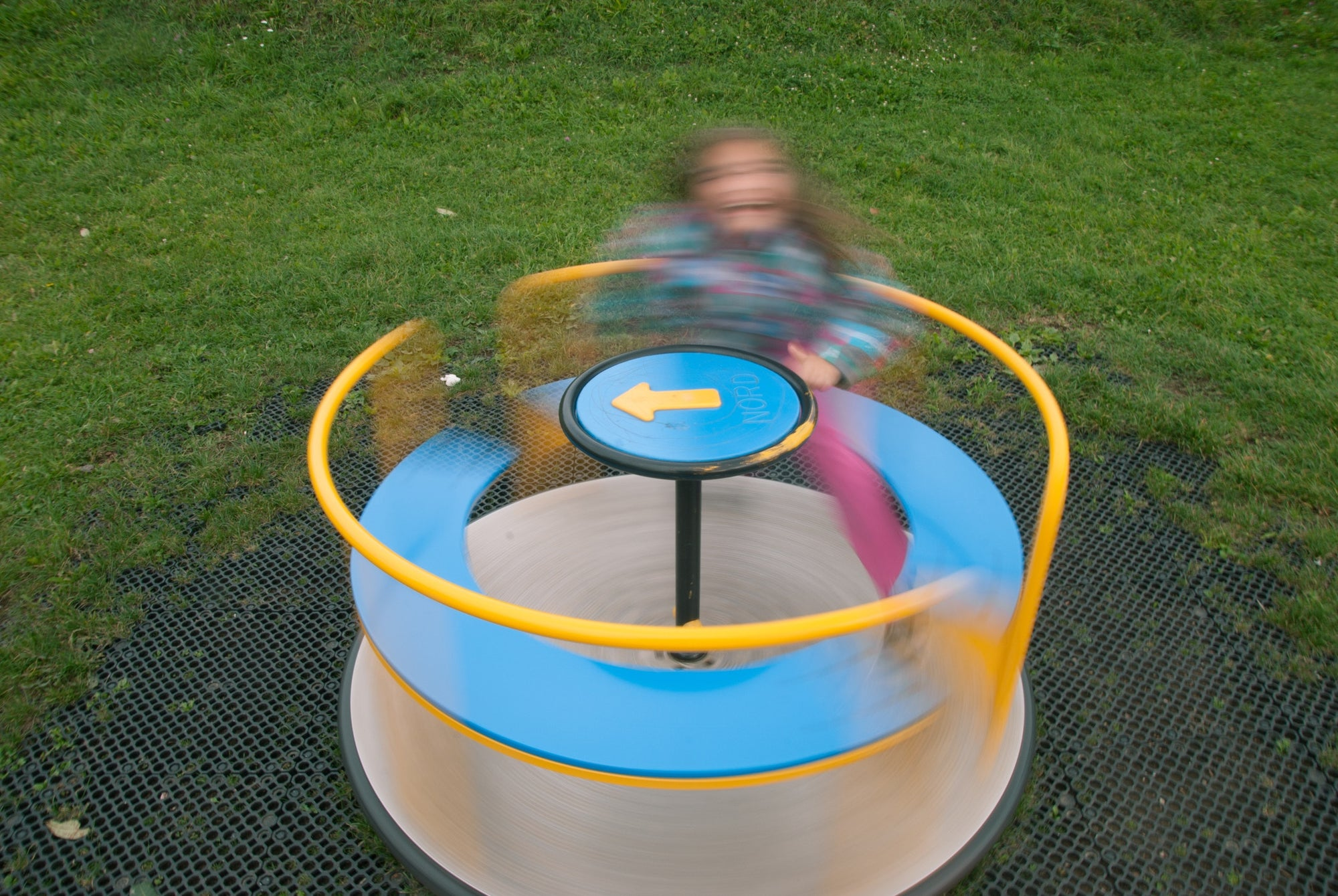 child spinning on playground roundabout