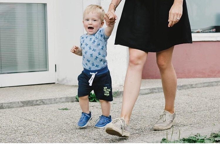 Baby child holding mother hand walking on road
