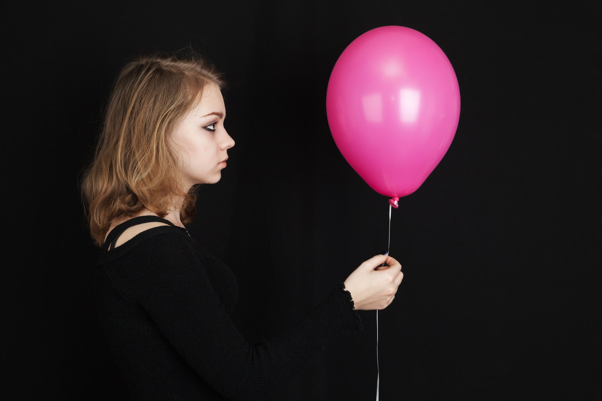 Young woman holding colorful pink balloon