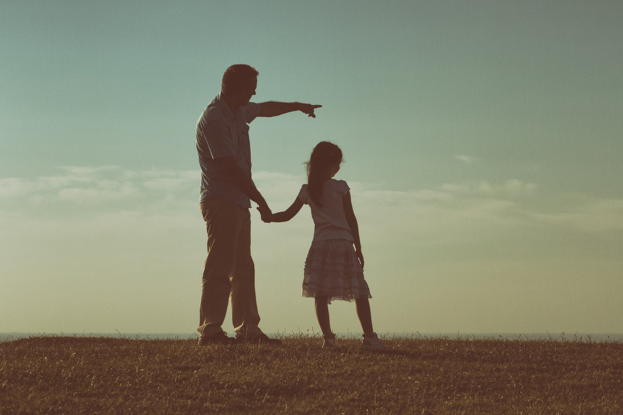 Father and daughter holding hands standing on a hill with nature lanscape back view.