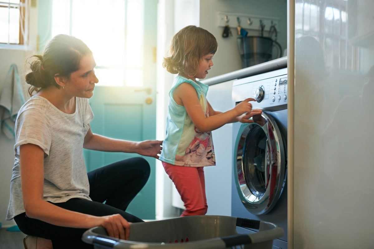 Little girl helping her mother to do laundry