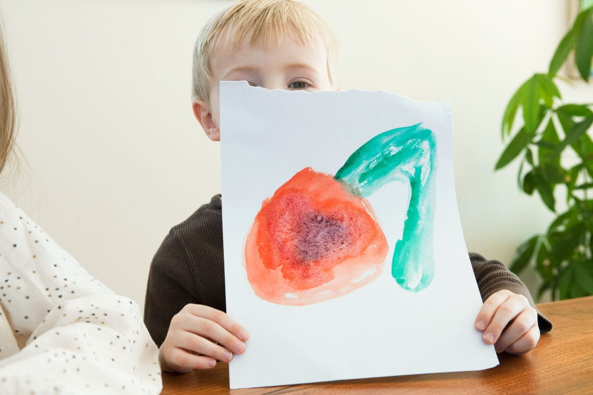 child showing his painting.