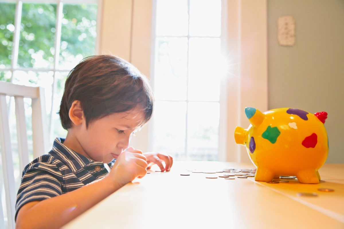 young boy counting his piggy bank money