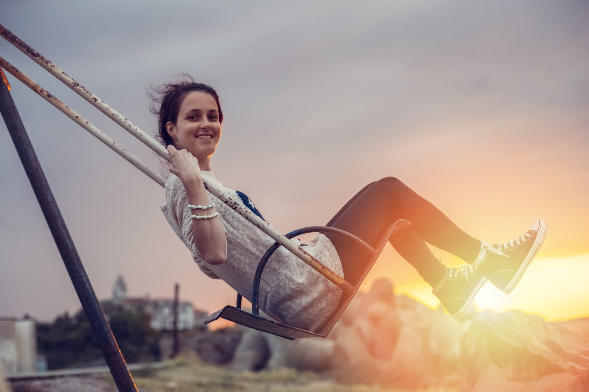 pretty girl swinging on a swing in a park