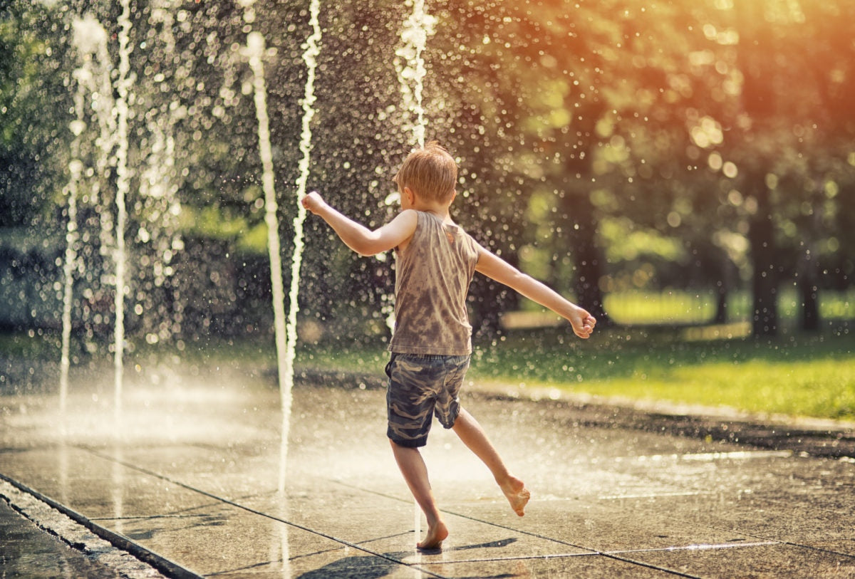 boy playing with water from a fountain