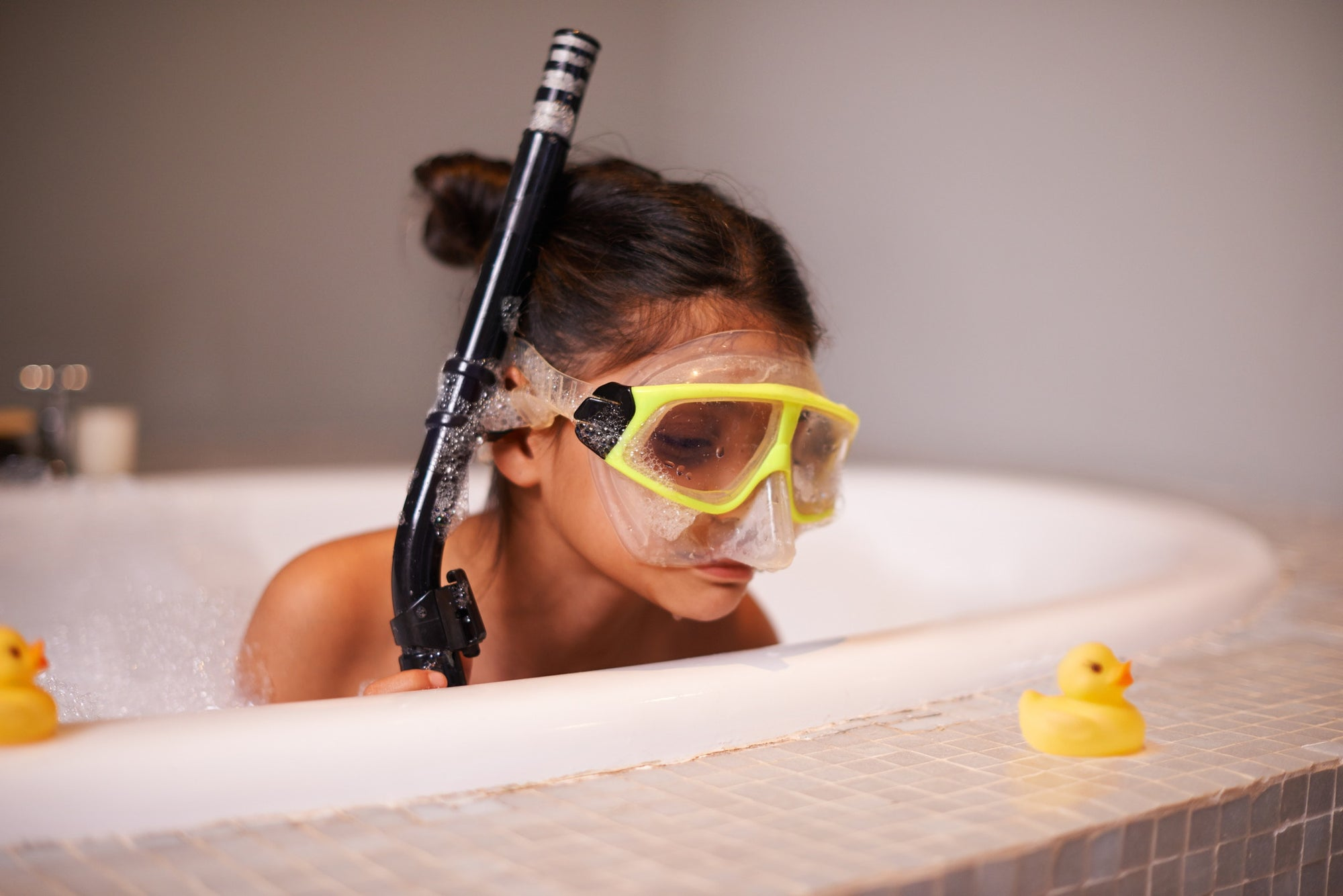 kid on a tub with breathing tube and swim googles