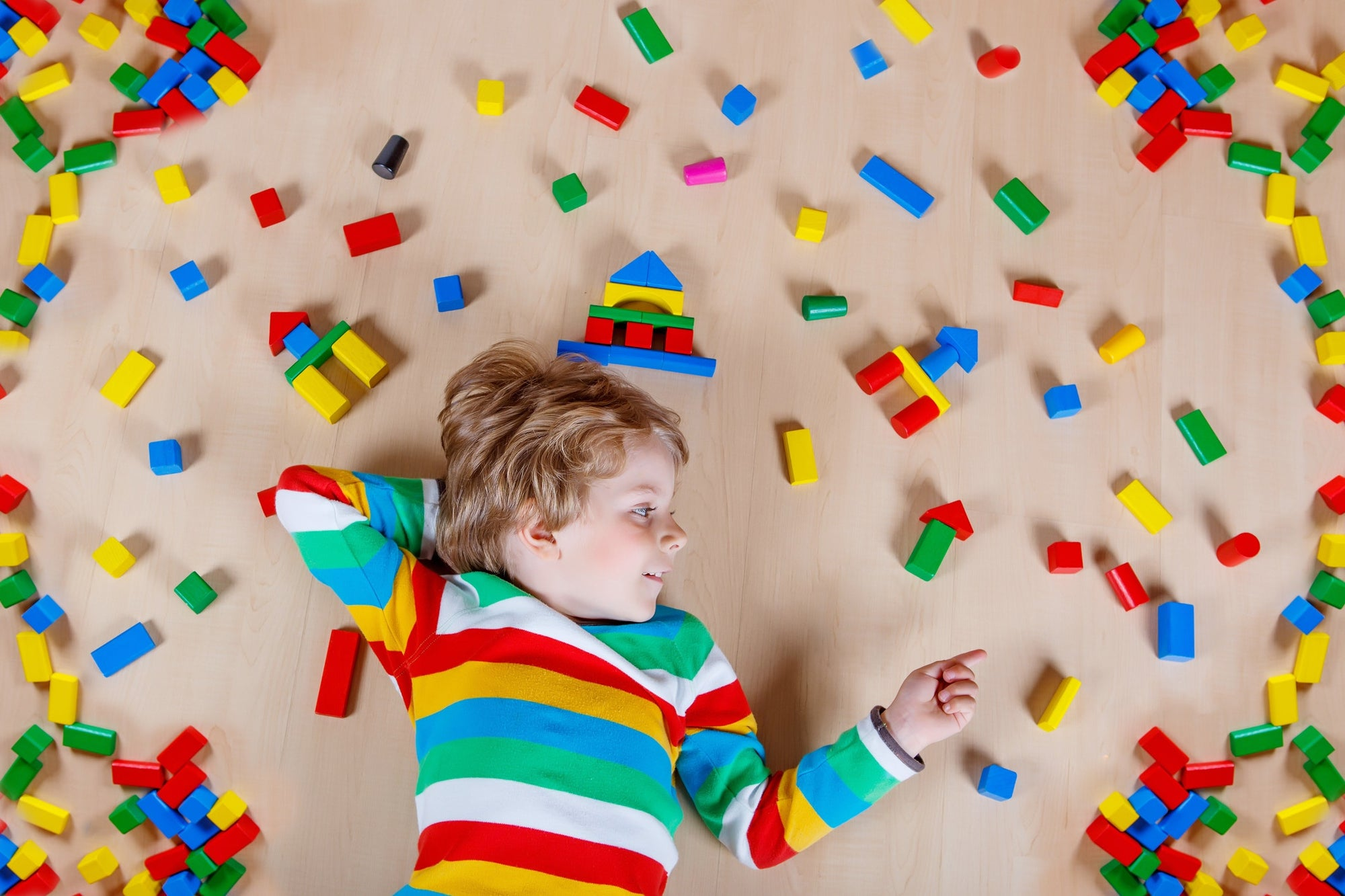 boy lying on the floor with blocks