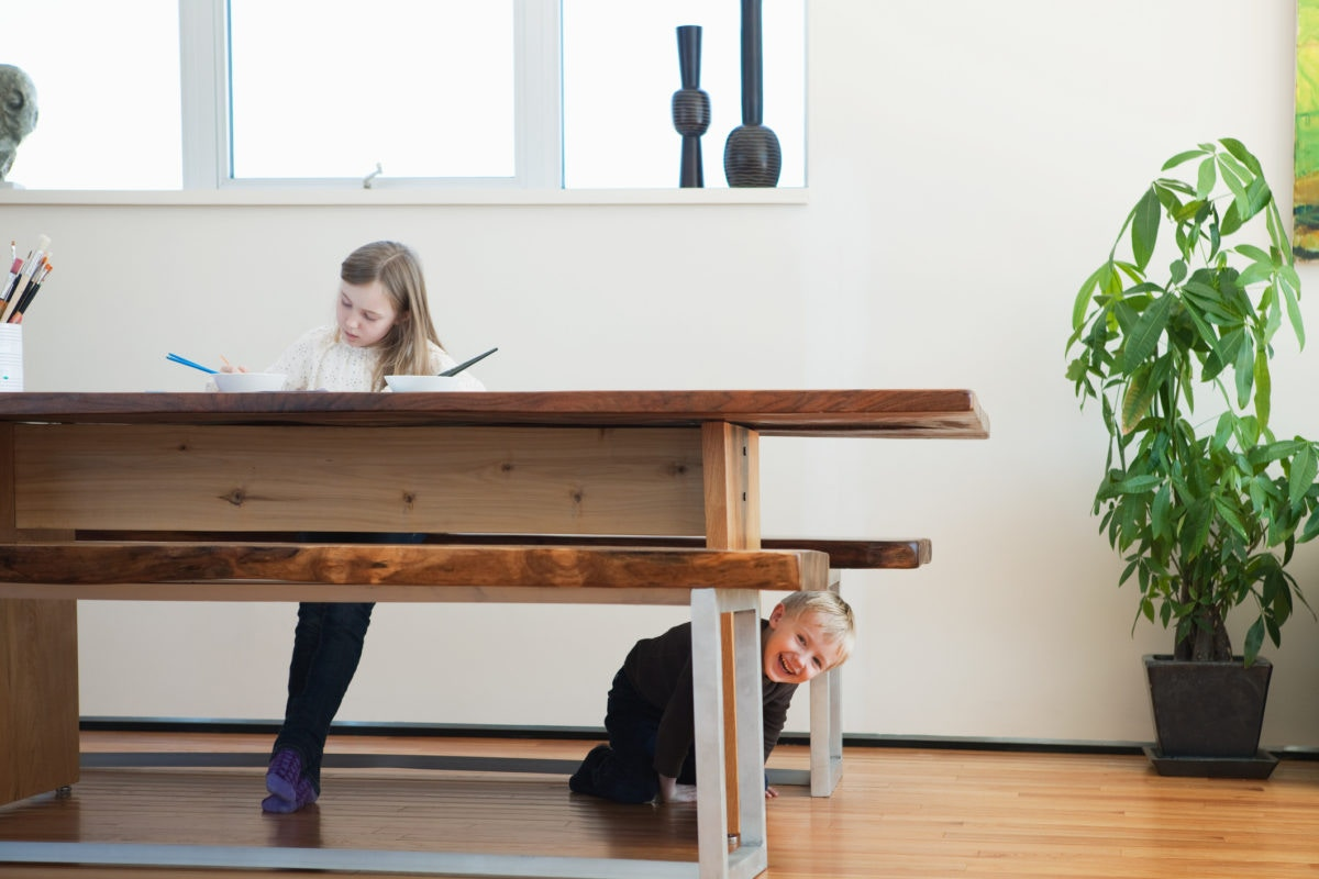 Girl is sitting on a table doing something while boy is sitting down side of a table by sneaking outside