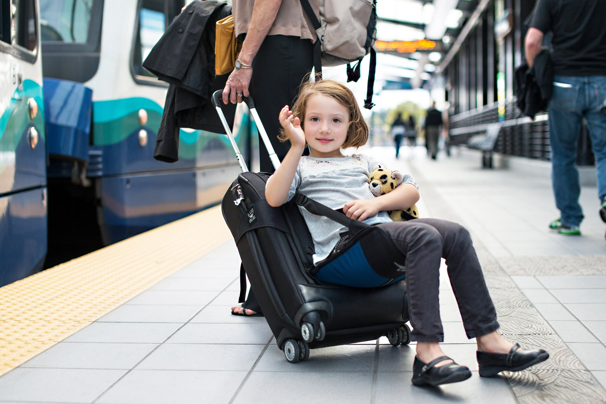 little girl sitting on suitcase seat