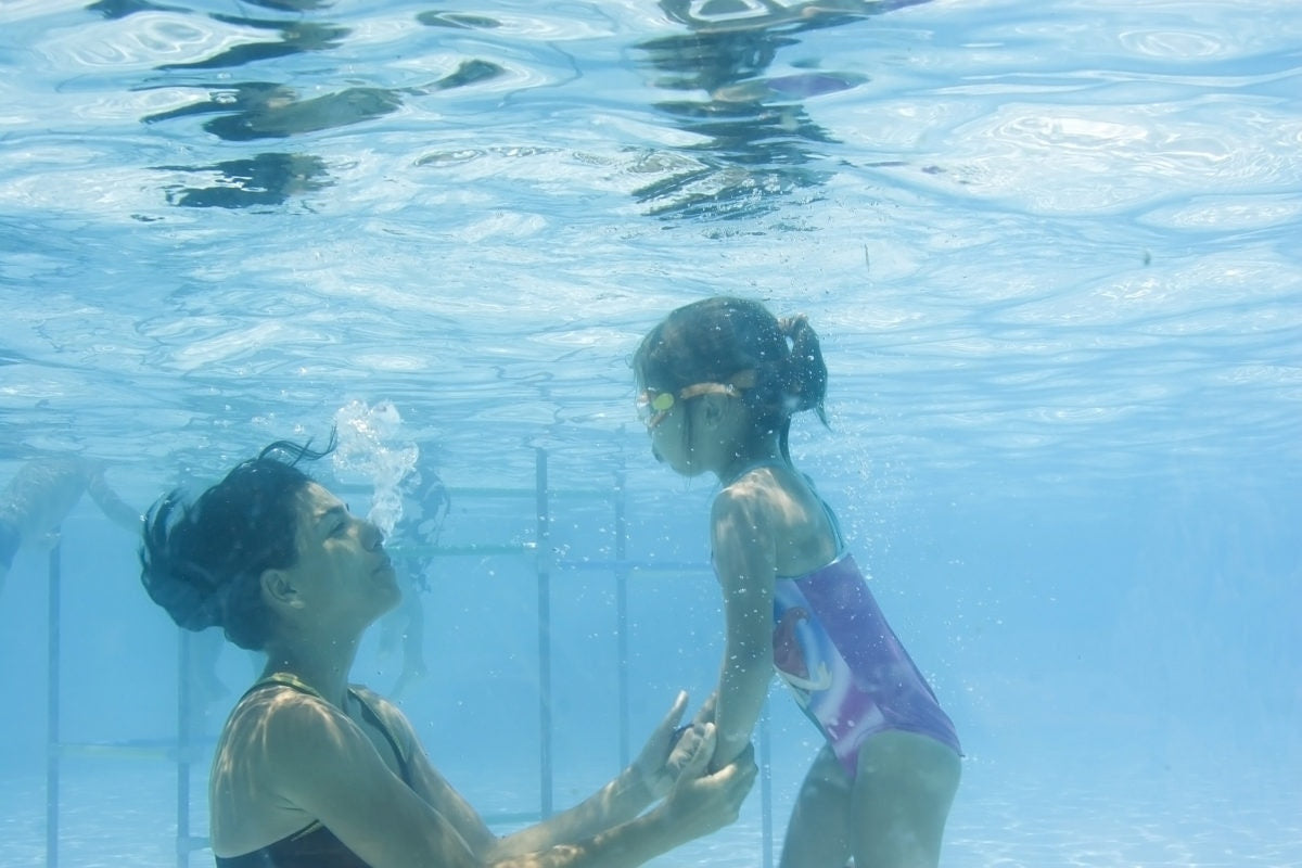 Mother and daughter playing in a swimming pool