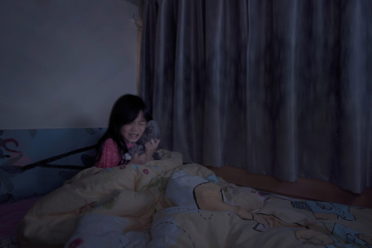 little girl with toy crying in the bed