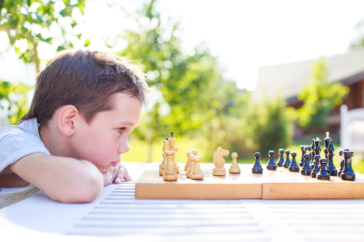 Young boy playing chess, staring at pieces on board,close-up