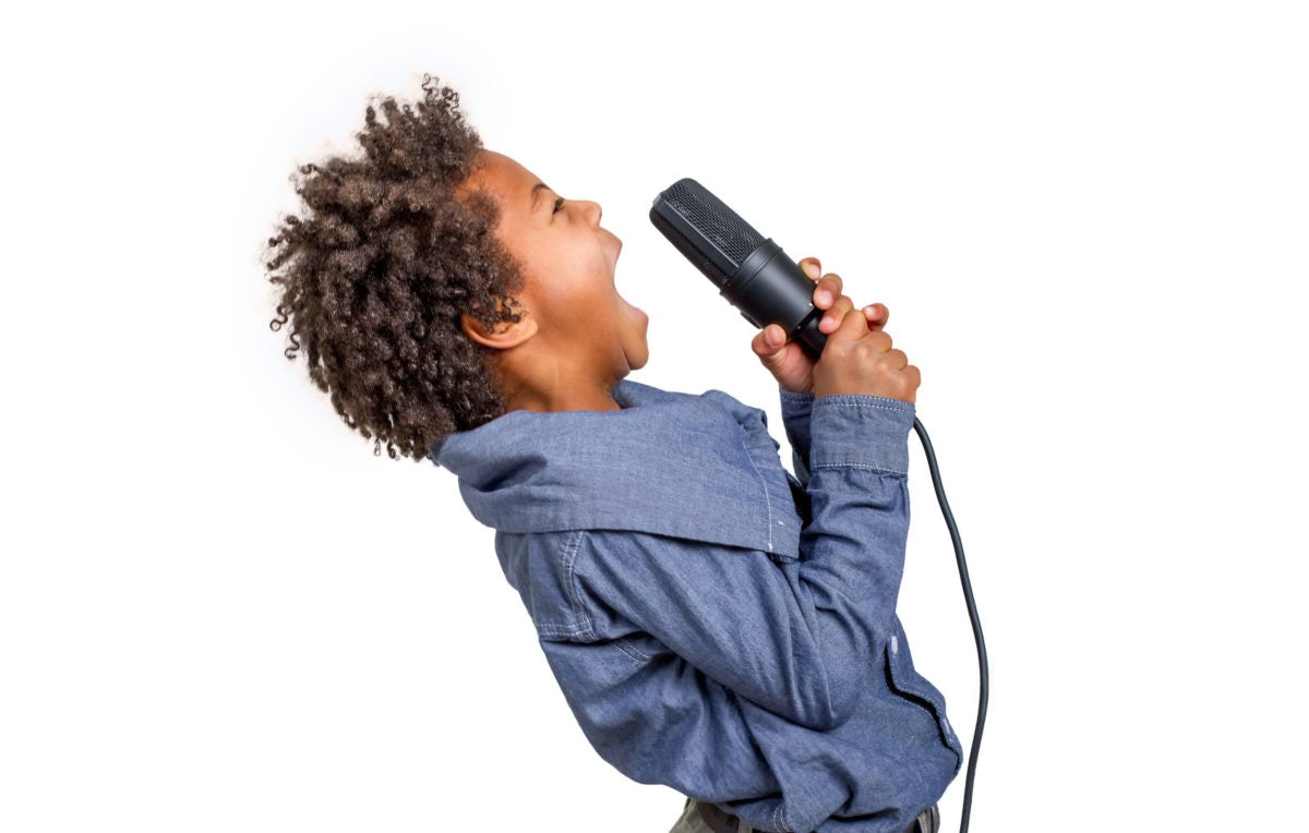 A kid singing a song holding  a microphone