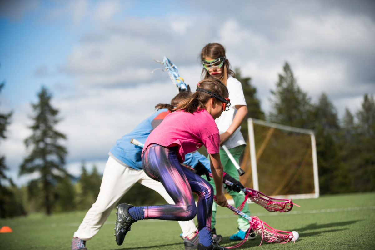 girls playing hockey outdoors