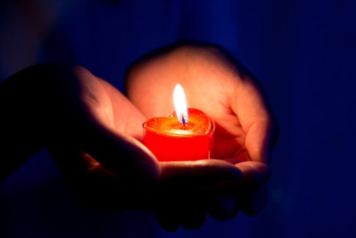 Hand holding a burning candle in dark