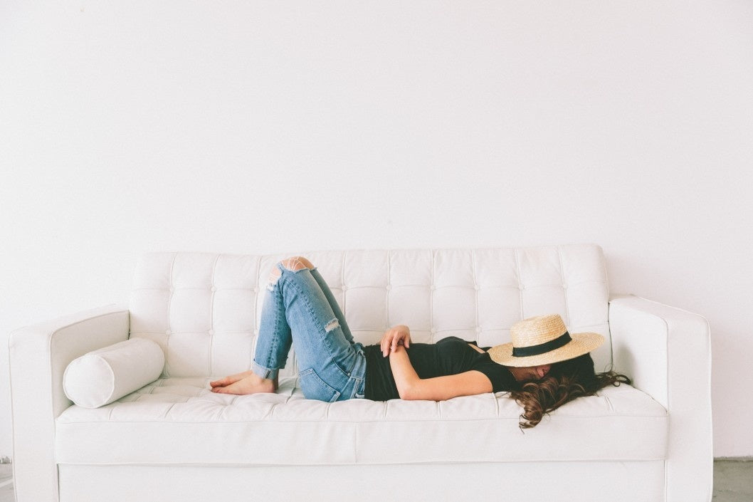 young woman sleeping on a bright white couch with a hat covering her face.