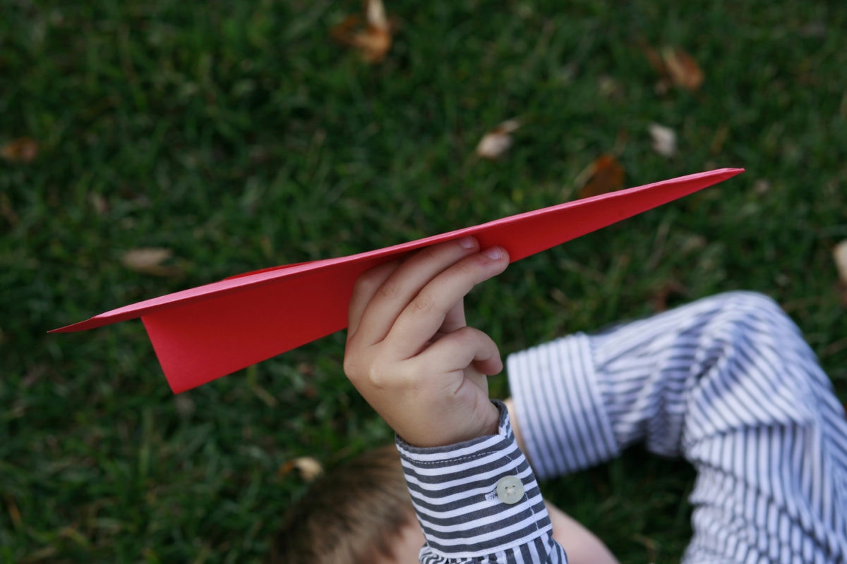 kid playing with paper airplane