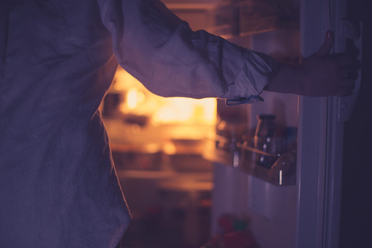 woman opening fridge at night