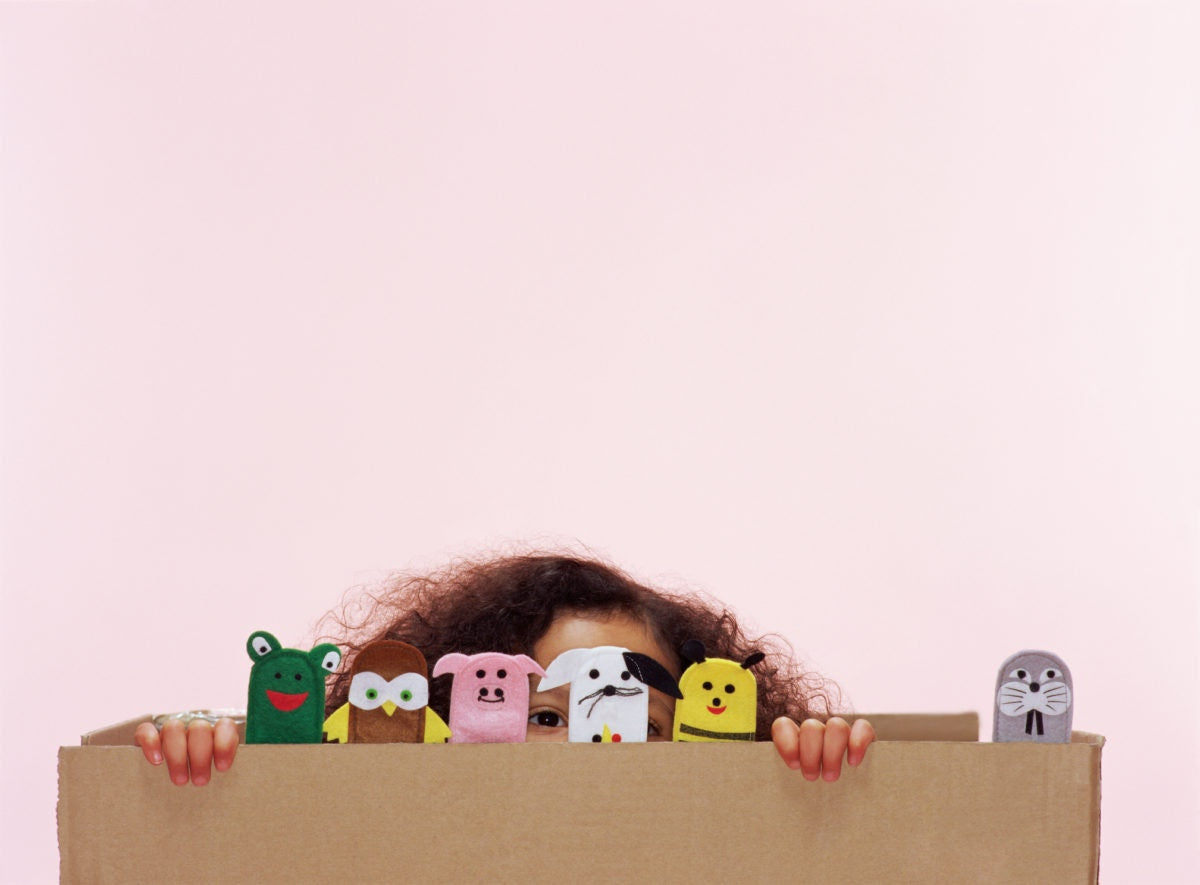 girl peeping above a box with finger puppets