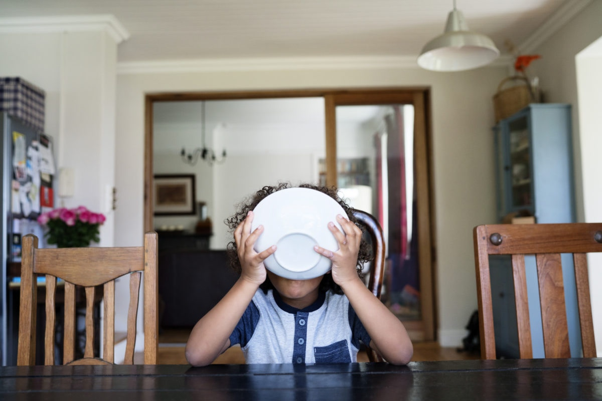 kid at a table holding a bowl of cereal