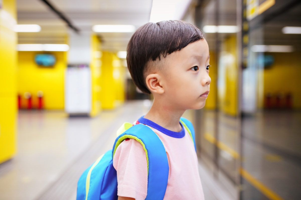Japanese boy looking at something wearing school bag
