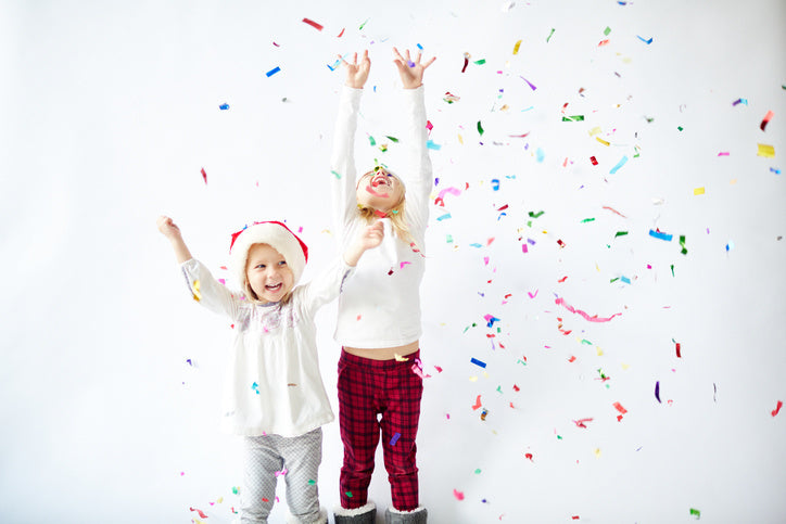 two young girls celebrating with confetti in the air
