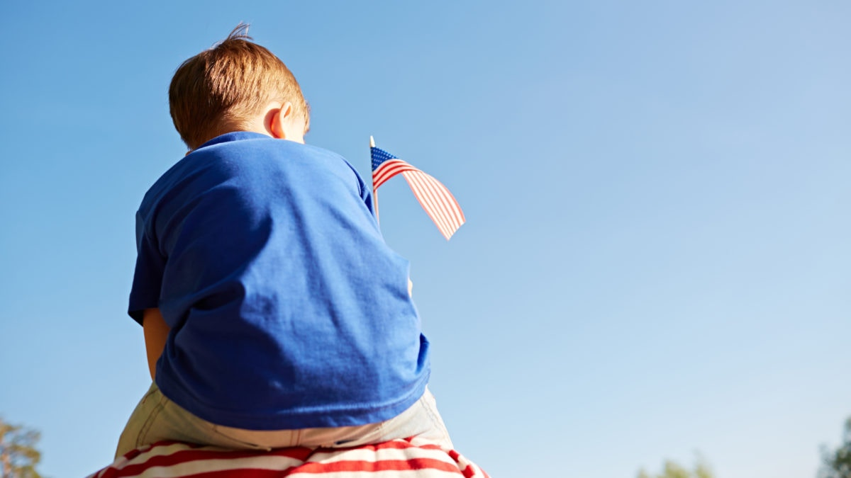 Boy sitting on a shoulder by holding US flag