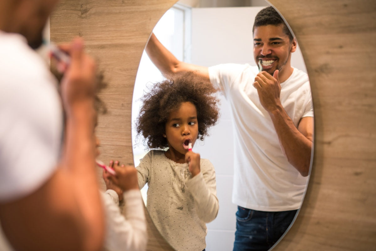 A Guy and child is brushing infront of mirror